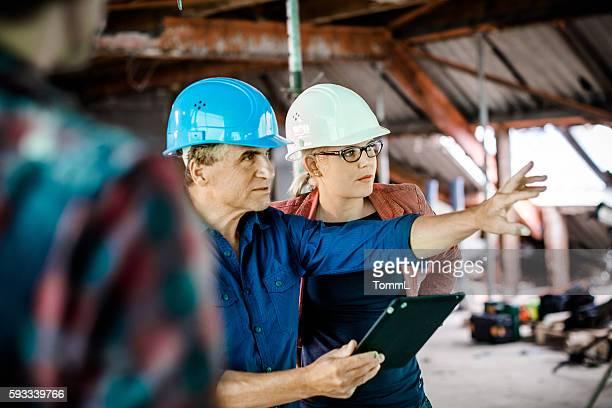 Weibliche Architekten, Bauarbeiter auf Haus diskutieren.