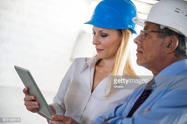Feminino Arquiteto e Trabalhador da Construção Civil a discussão no local
