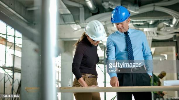 Female architect and male project manager discussing at construction site