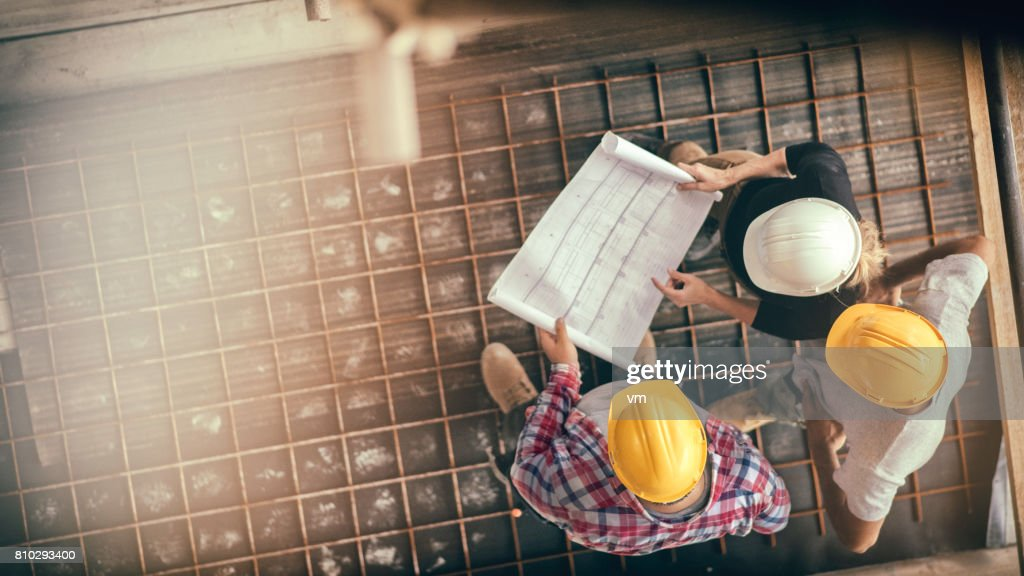 Female architect and two consruction workers on a construction site : Stock Photo