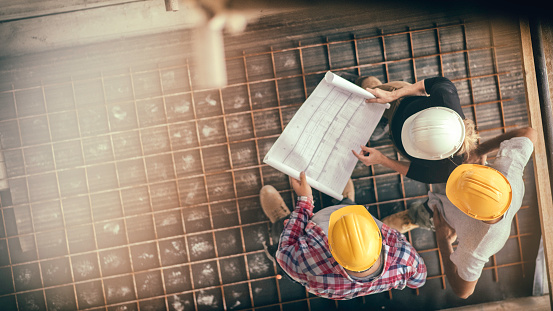 Female architect and two consruction workers on a construction site 810293400