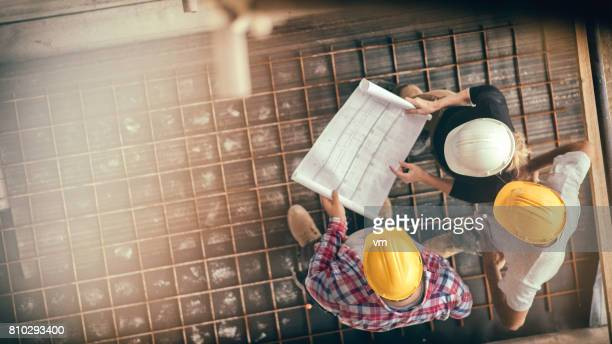 female architect and two consruction workers on a construction site - built structure stock pictures, royalty-free photos & images