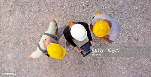 Female architect and two construction workers checking plan on digital tablet and pointing at building to check progress