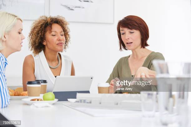 Female architect explaining architectural model on table in team meeting