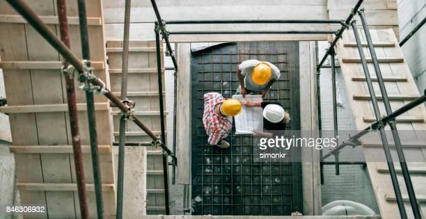 Architektin, Bauleiter und Vorarbeiter, die am Ende der Treppe Gerüst stehen Einzelheiten des Plans zu erklären