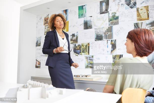 Female architect explaining to colleague in office meeting