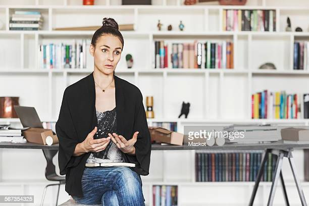 Female architect gesturing while explaining at home office