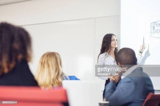 Female architect giving presentation at business meeting