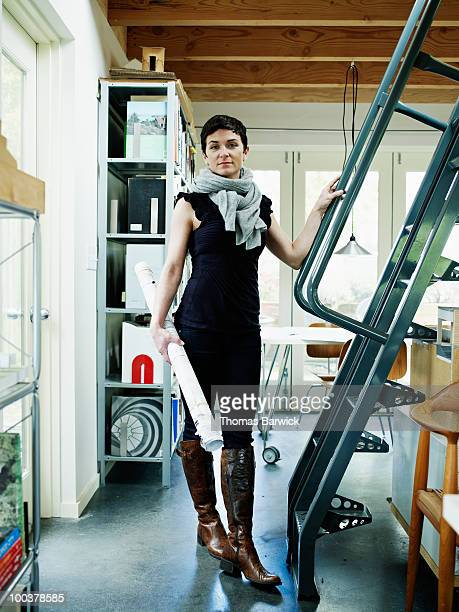 female architect in home office holding plans - 女性建築家 ストックフォトと画像