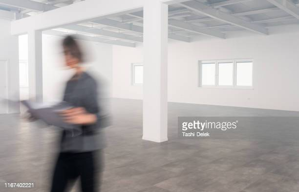 female architect in modern empty office, blurred motion - real estate office stock pictures, royalty-free photos & images