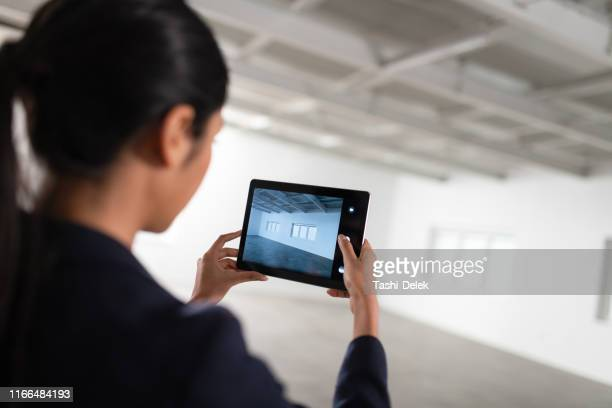 female architect in modern empty office looking at plans - real estate developer stock pictures, royalty-free photos & images
