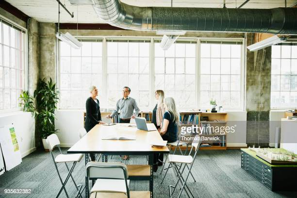 Female architect leading planning meeting at conference table in design office