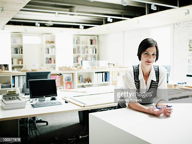 Female architect leaning on table in office