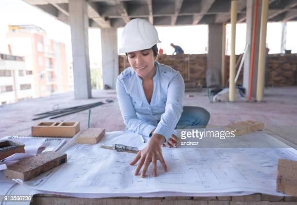 architektin, blick auf eine blaupause auf einer baustelle - technische zeichnung stock-fotos und bilder