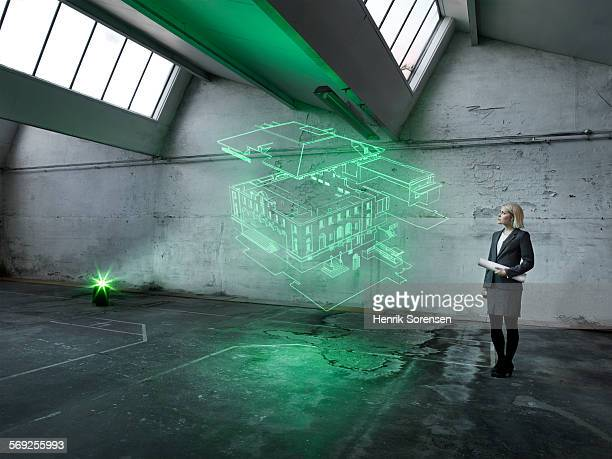 female architect looking at a holographic house - hologram stock pictures, royalty-free photos & images