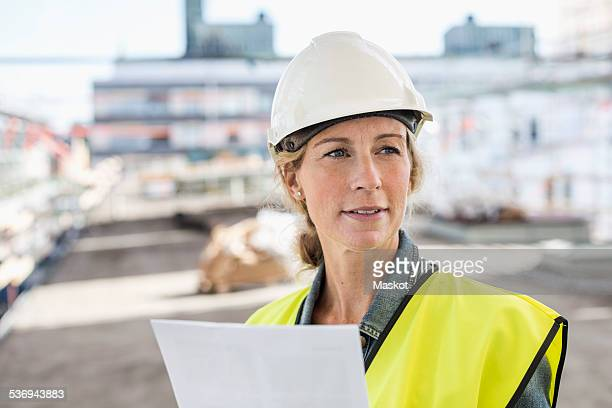 Female architect looking away while working at construction site