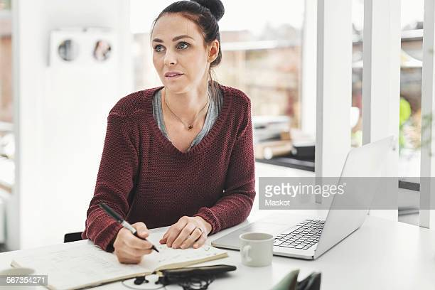 Female architect looking away while working at table in home office