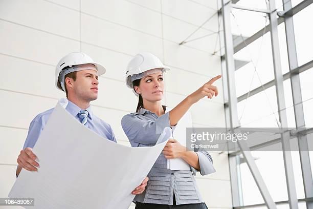 Weibliche Architekt zeigt etwas zu einem männlichen Kollegen