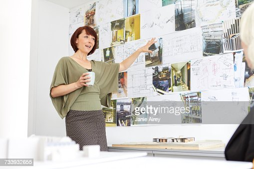 Female architect pointing to mood board in office presentation