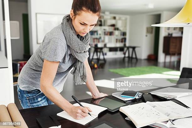Female architect reading book at table in home office