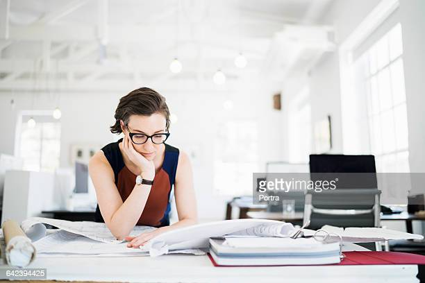 Female architect reviewing blueprints in office
