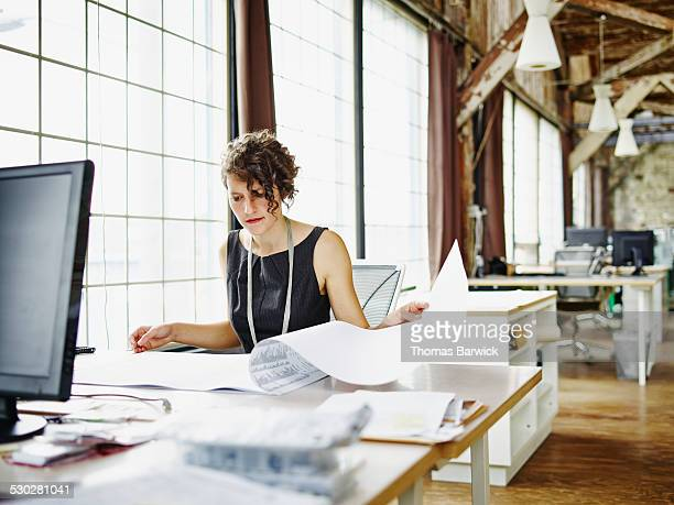 Female architect reviewing project plans at desk