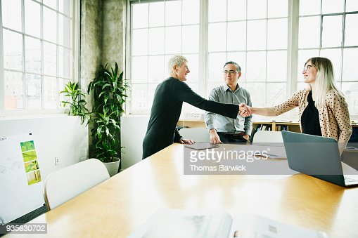 Female architect shaking hands with client before project meeting in office conference room