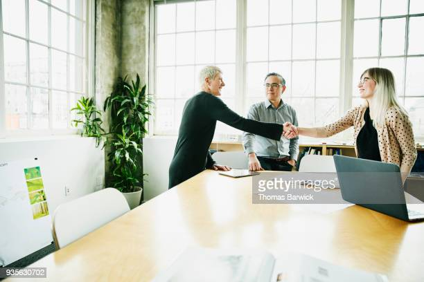 female architect shaking hands with client before project meeting in office conference room - wood table top stock photos and pictures