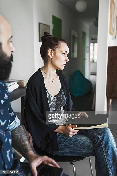 Female architect sitting with male colleague at home