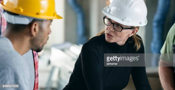 female architect talking to workers at construction site, discussing plans set on table - incidental people stock pictures, royalty-free photos & images