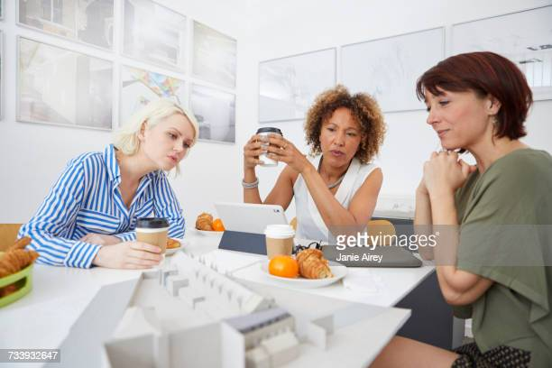 Female architect team looking at architectural model on table