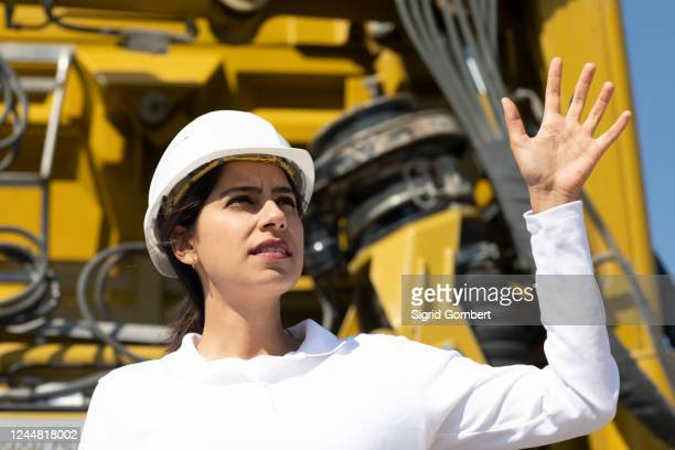 female architect wearing white hard hat working on construction site. - sigrid gombert stock pictures, royalty-free photos & images