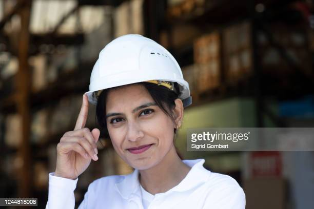 female architect wearing white hard hat working on construction site, smiling at camera. - sigrid gombert stock pictures, royalty-free photos & images