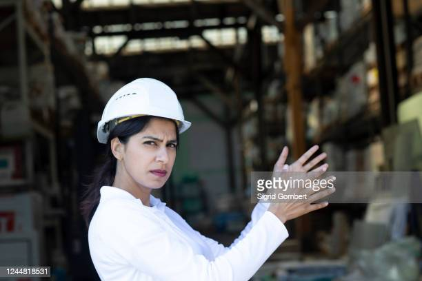 female architect wearing white hard hat working on construction site, looking at camera. - sigrid gombert stock pictures, royalty-free photos & images