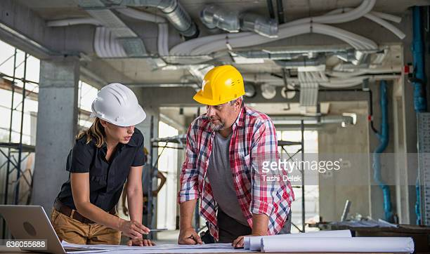 female architect with construction worker - surveyor stock photos and pictures