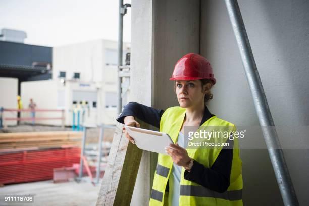 female architect with digital tablet at construction site - vorarbeiter stock-fotos und bilder