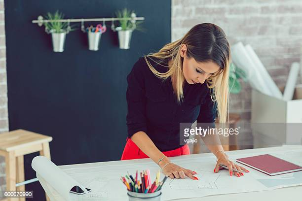 Female Architect Working In Her Office.