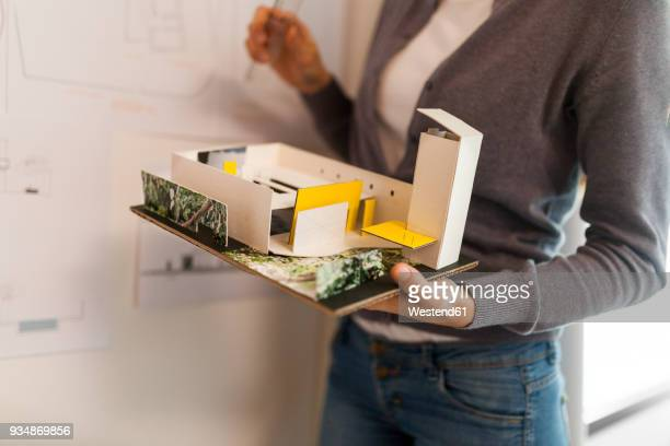 Female architect working on a project, holding architectural model