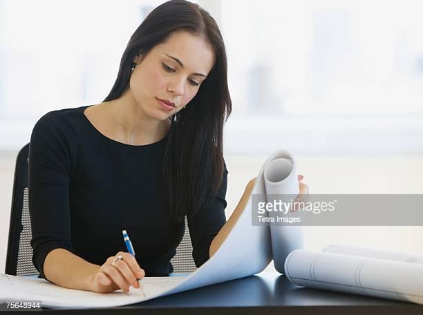Female architect writing on blueprints