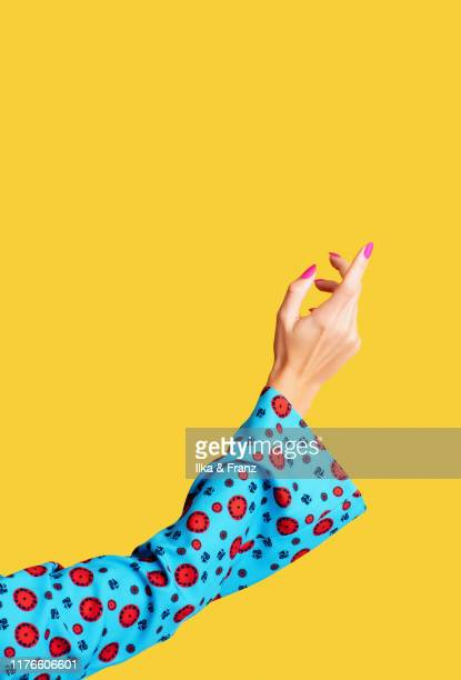 female arm and hand on yellow background - menselijke ledematen stockfoto's en -beelden