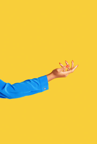 female arm and hand on yellow background - hand stock pictures, royalty-free photos & images