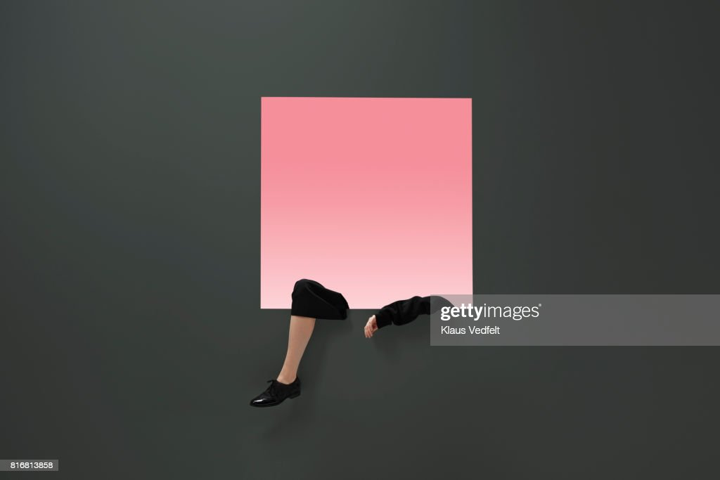 Female arm and leg, dangling from square opening in coloured wall : Stock-Foto