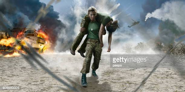 female army medic soldier carrying wounded soldier from desert battlefield - war stock pictures, royalty-free photos & images