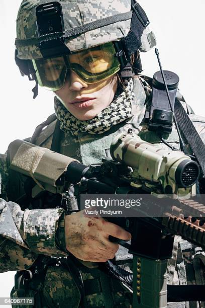 female army soldier carrying rifle standing against white background - ライフル ストックフォトと画像