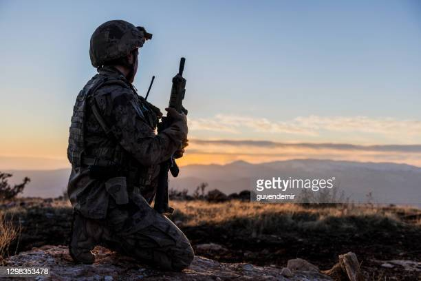 female army solider watching sunset sky in battlefield - army stock pictures, royalty-free photos & images