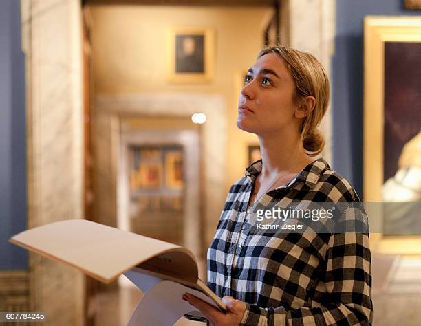 female art student at gallery, looking at painting - museum foto e immagini stock
