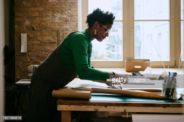 female artist concentrating while doing craft at table in living room - diversity stock pictures, royalty-free photos & images