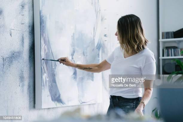 artista femenina creando arte - mujeres de mediana edad fotografías e imágenes de stock