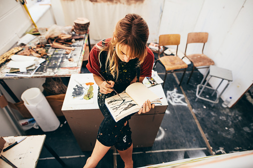 Female artist drawing pictures in her workshop 694858350