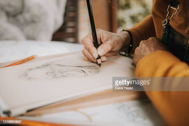 female artist drawing with colored pencils in her studio - artist stock pictures, royalty-free photos & images